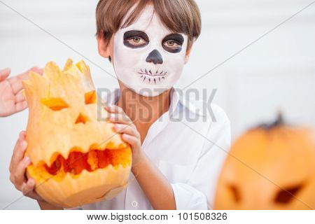 Cute male child in grease-paint is celebrating Halloween