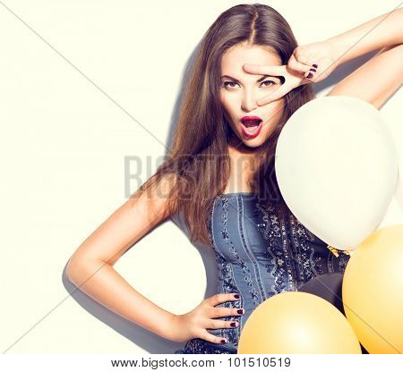 Beauty fashion brunette model girl with colorful balloons posing isolated on white background. Fashion model girl making v-sign or victory gesture. Perfect make up and manicure. Party celebration