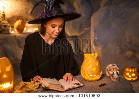 Attractive young evil witch is conjuring with aspiration