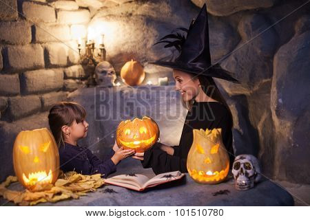 Attractive young female wizard is teaching her daughter