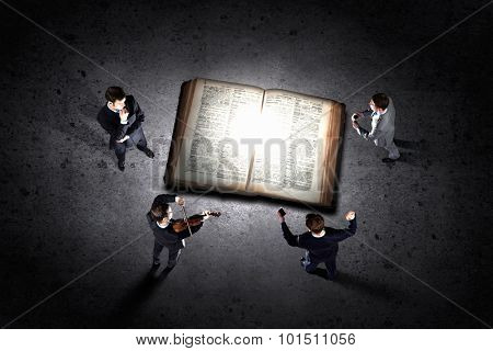 Top view of big old opened book and businesspeople around it