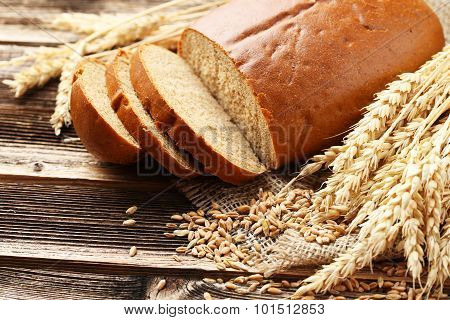 Ears Of Wheat With Wheat Grains And Bread On Brown Wooden Background