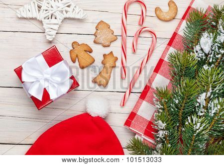 Christmas gift box, santa hat, gingerbread cookies and snow fir tree. View from above over white wooden table background