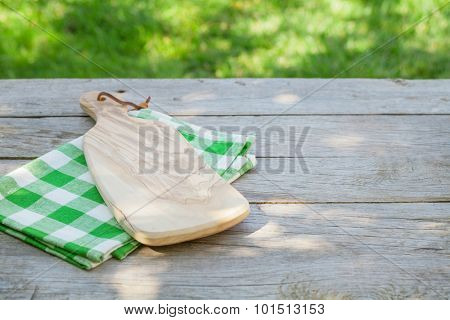 Empty wooden garden table with cutting board over tablecloth with green sunny bokeh background