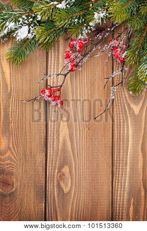 Christmas wooden background with snow fir tree and holly berry
