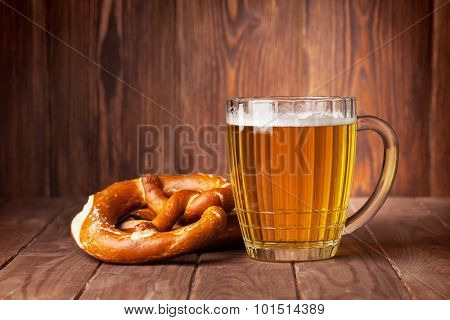 Lager beer glass and pretzel on wooden table. View with copy space