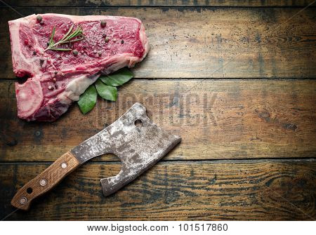 Raw beef steak with spices and meat hatchet on a wooden board.