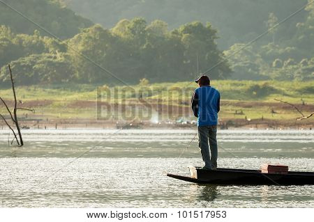 Angler Standing Fishing On A Boat In The Lake.