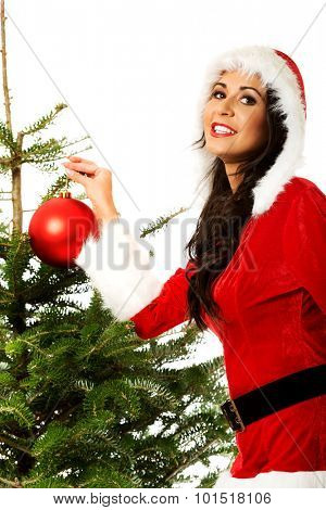 Smiling woman wearing santa clothes decorating christmas tree.