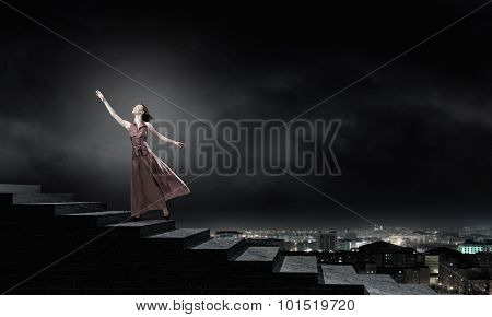 Young blond woman in dress walking up the stairs