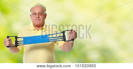 Elderly man with chest expander over green background.
