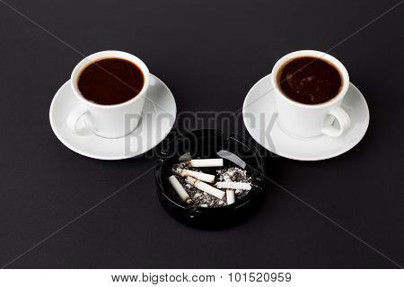Cups of coffee with ashtray