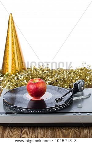 Shiny party hat with record player and apple