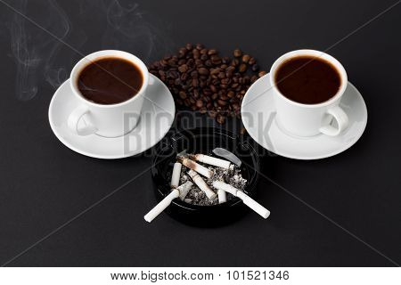 White cups of coffee with ashtray and beans