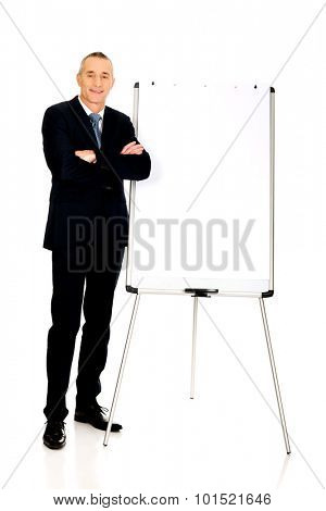 Mature businessman standing near flip chart.