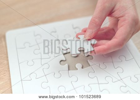 Female Hand Putting A Missing Piece Into Jigsaw Puzzle