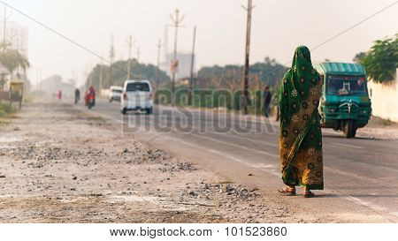 Indian woman walking on the road.
