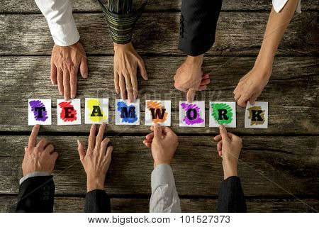 Top View Of Eight Business People Assembling The Word Teamwork