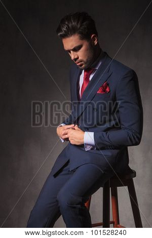 Young business man looking down while closing his jacket.