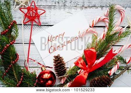 Christmas composition made up of conifer branches, cones, decorative bubble, stars, beads, candy canes and greeting card on wooden background