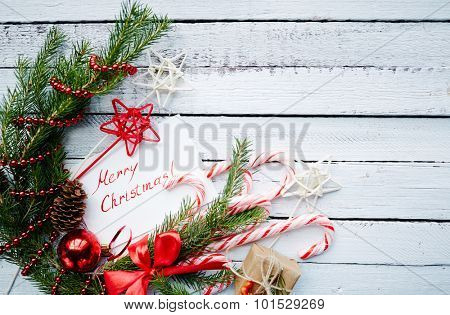 Christmas composition of conifer branches, cones, decorative bubble, stars, beads, candy canes, greeting card and small giftbox