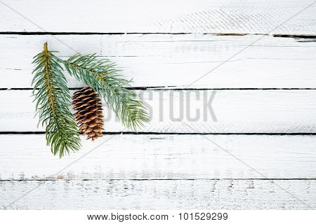 Firtree cone and conifer over wooden background