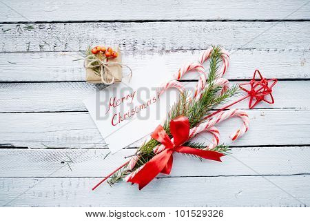 Christmas bouquet, greeting card and small giftbox on wooden background
