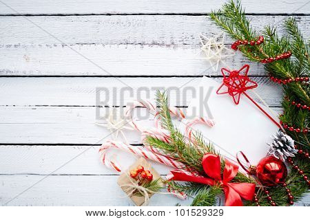 Composition of conifer branches, cones, decorative bubble, stars, beads, candy canes and small giftbox on wooden background