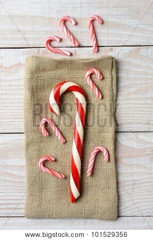Overhead view of different sized Candy canes on a burlap bag and three on wood surface. On a rustic wood table in vertical format