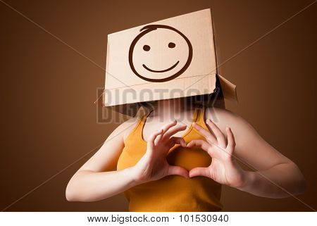 Young girl standing and gesturing with a cardboard box on her head with smiley face