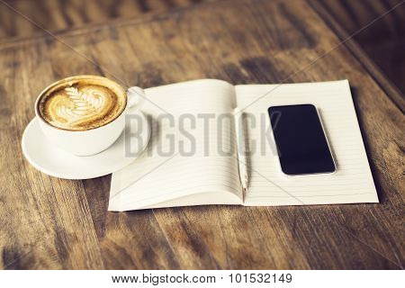 Blank Cell Phone, Cup Of Coffee And Diary On A Wooden Table