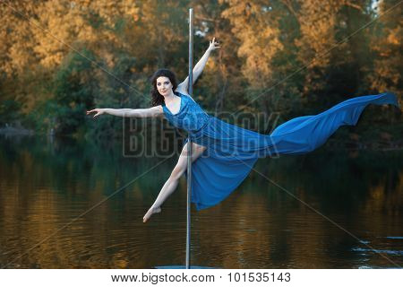Girl In Flowing Dress Is Dancing Around A Pole Dance.