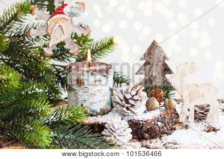 Christmas decorations with burning candle, wooden toys,fir branches and pine cones