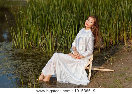 Beautiful Girl Sits On Shore Of The Lake.