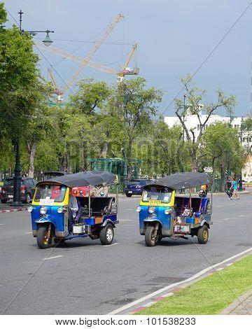 Tuk-tuks Passing Royal Palace In Bangkok