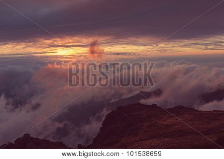 Beautiful sunset on the hill above clouds