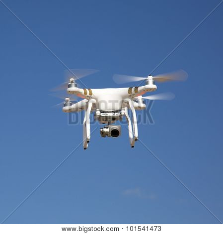 Drone Hovering Against Blue Sky On Sunny Day