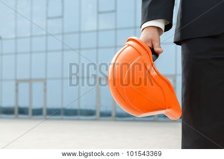 Architect holding protective helmet