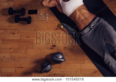 Woman Relaxing After Workout With Exercise Equipments