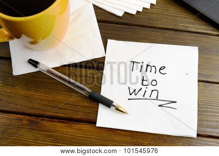 Time to win think positive -  handwriting on a napkin with a cup of coffee
