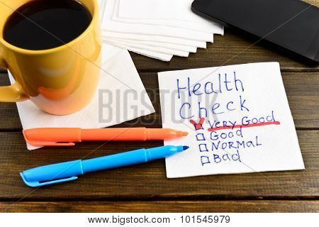 health test -  handwriting on a napkin with a cup of coffee and phone