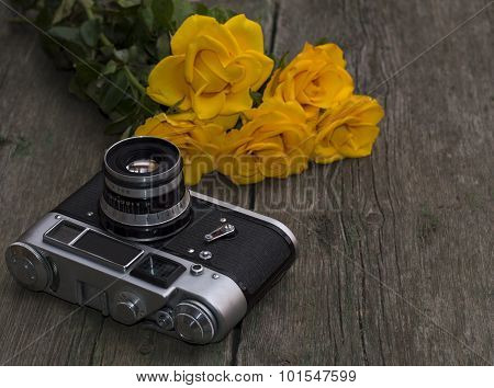 The Old Film Camera And Bouquet Of Yellow Roses On A Wooden Background
