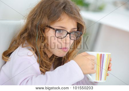 School girl holding stripy cup
