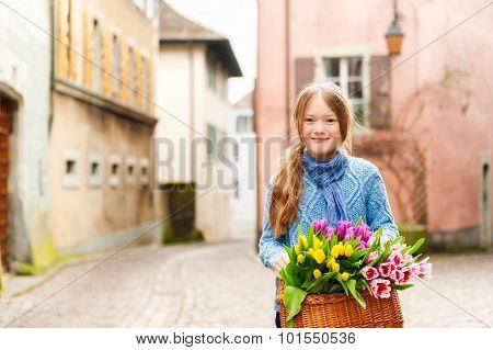Outdoor portrait of adorable little girl of 7 years old walking in old town