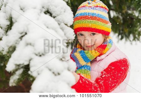 Winter portrait of a cute little girl under the snowfall, wearing red pullover, colorful hat