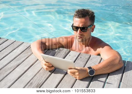 Man with digital tablet computer by the pool