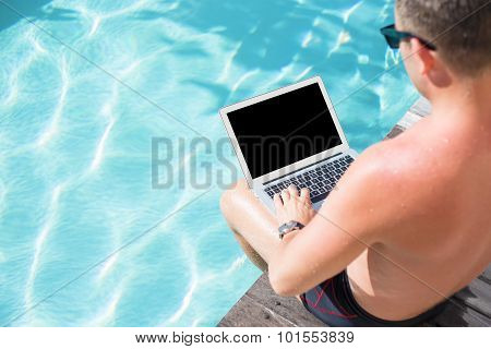 Man with computer sitting by the pool