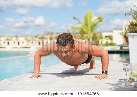Man exercise and doing push ups by the pool
