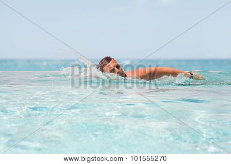 Man swimming in infinity pool