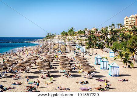 People Sunbathing In The Picturesque El Duque Beach